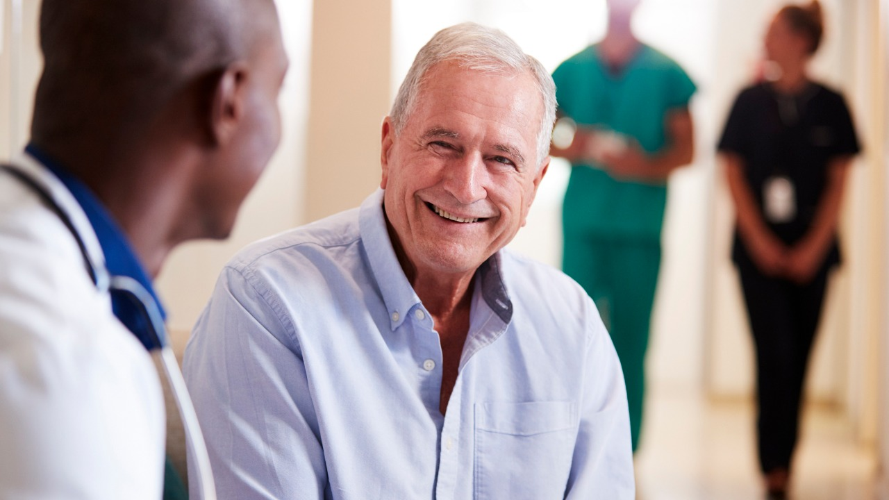doctor-welcoming-to-senior-male-patient-being-admitted-to-hospital-picture-id1147980079
